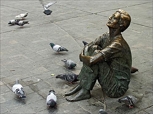 Una estatua de un niño viendo a lo alto de la Torre Nueva en Zaragoza